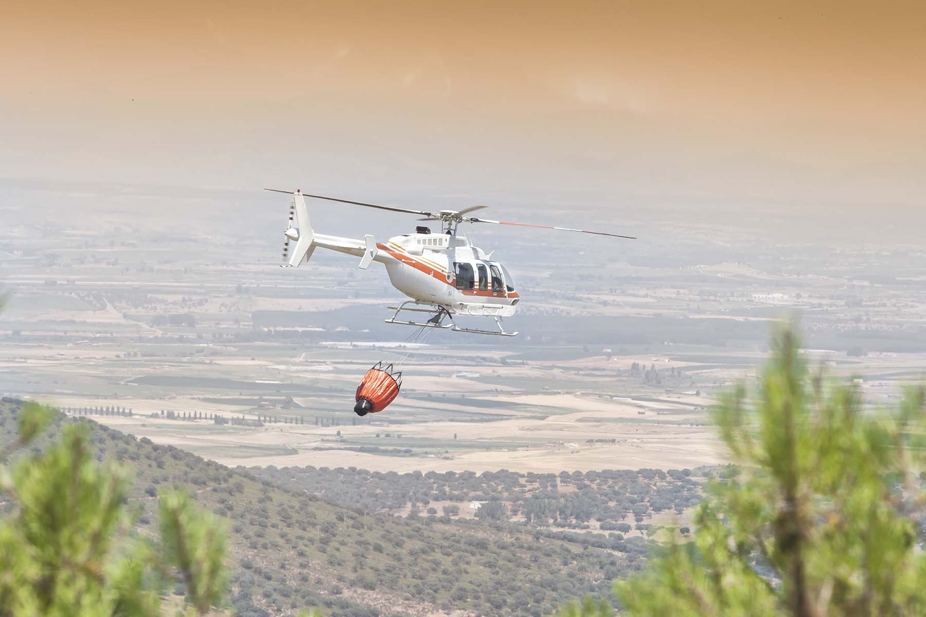 helicopter dropping water on a wildland fire