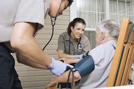 paramedics treating an older patient at home