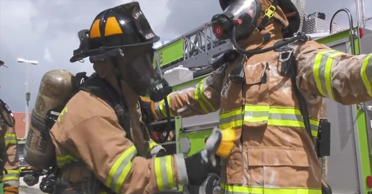 firefighter helping another firefighter disinfect PPE