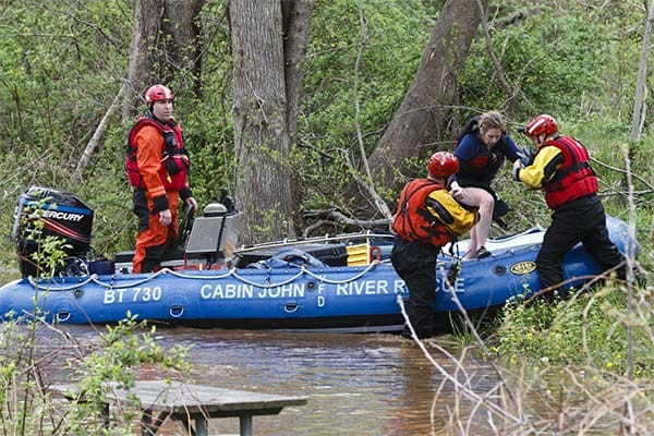 rescue workers helping a stranded kayaker off a boat