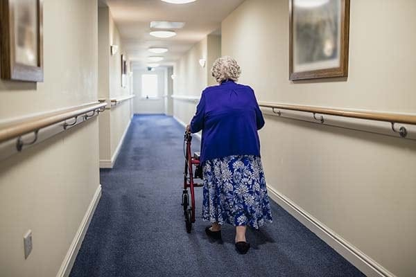 senior woman with a walker in a care home
