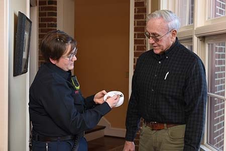 firefighter showing smoke alarm battery compartment to an older adult