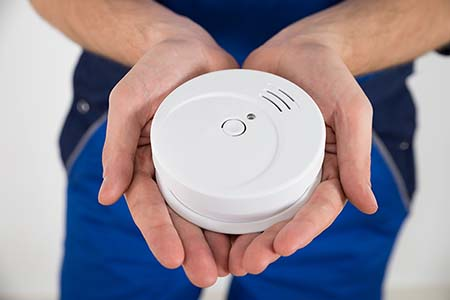 man holding a smoke alarm in his hands