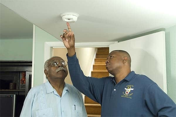 firefighter and an older man testing a smoke alarm