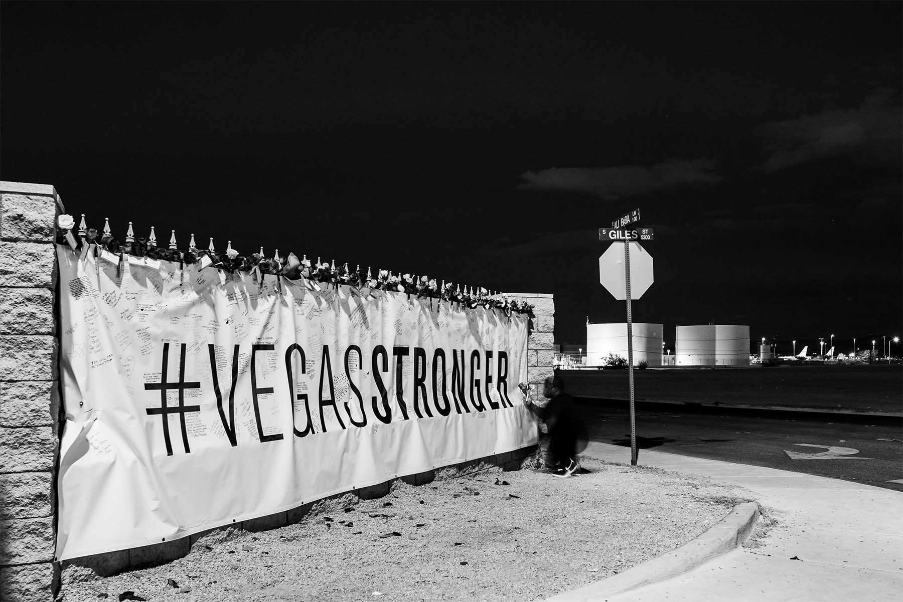 a man writes on the Vegas Stronger sign