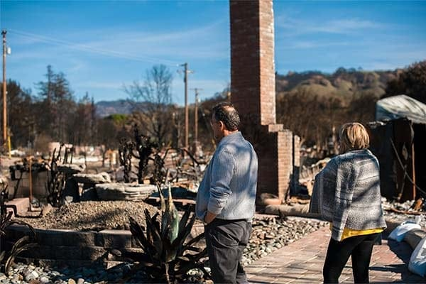 photo of a couple looking at their home destroyed by fire