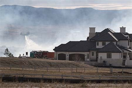photo of a home with wildfire smoke and a helicopter in the background