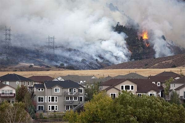 photo of a wildfire on a hillside with houses in the foreground