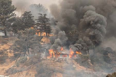 homes burning on a hillside during a wildfire