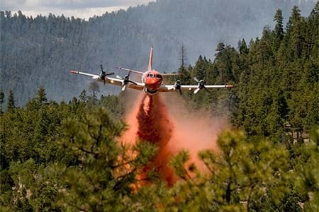 plane dropping fire retardant on a fire