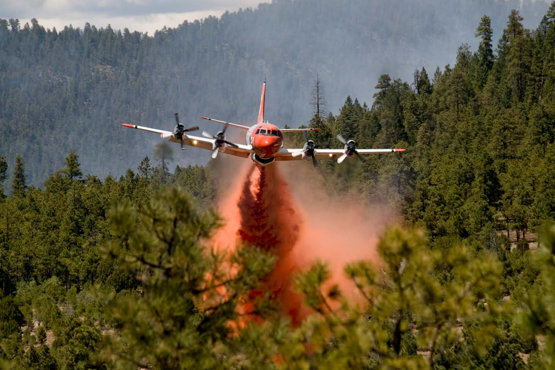 plane dropping fire retardant on a wildfire
