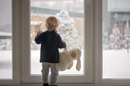 child looking outside at the snow